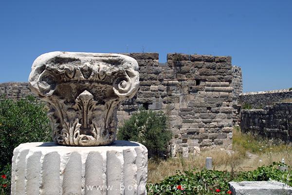 Starożytna grecka kolumna na tle średniowiecznych murów.