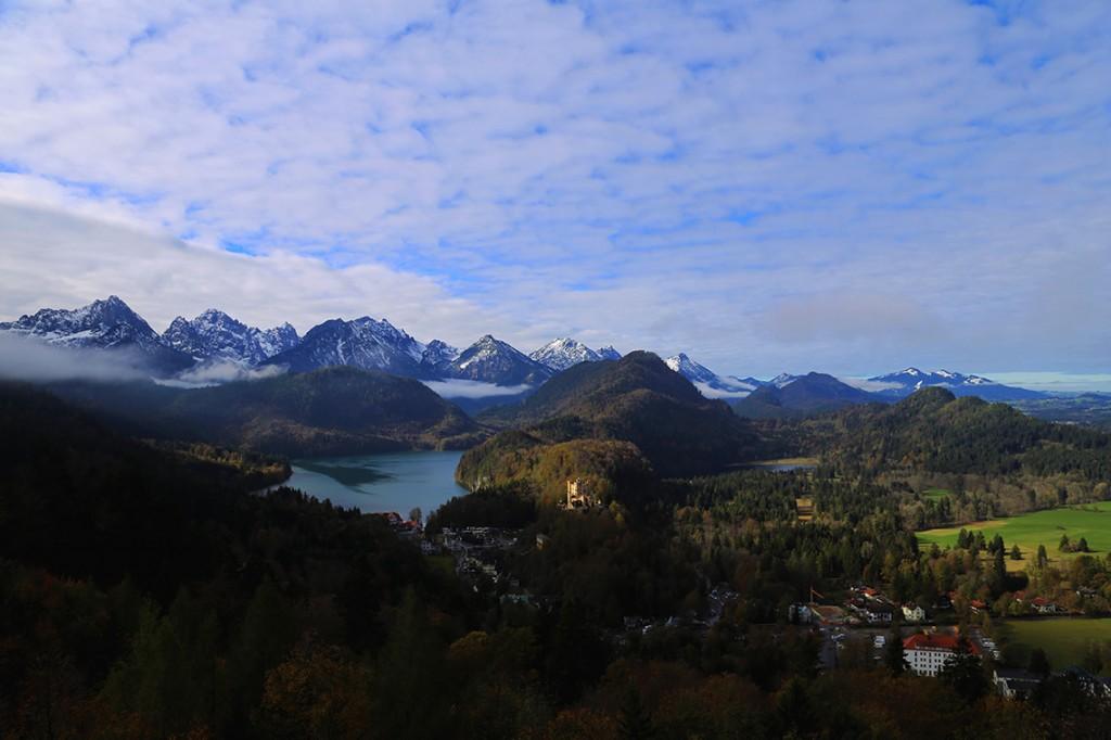 Przepiękny widok z balkonu zamku Neuschwanstein: Alpy, lasy, jezioro Alpsee i zamek Hohenschwangau.
