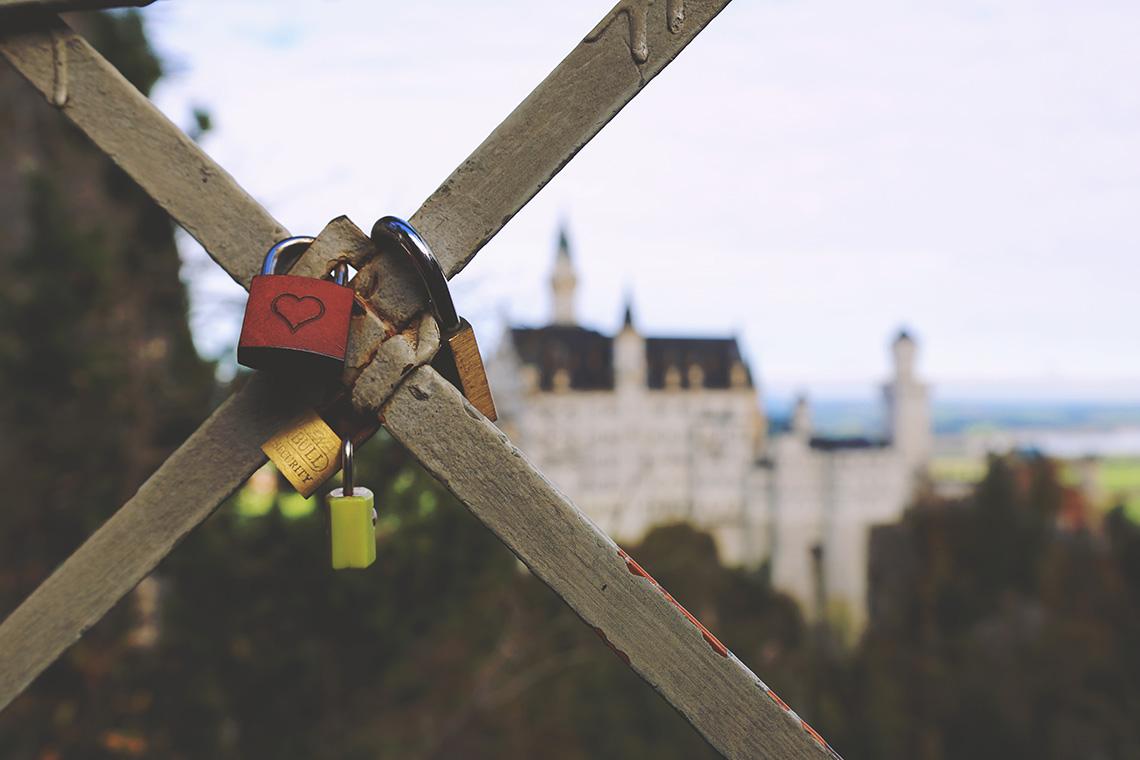 Kłódki zawieszone na moście Marienbrücke. W tle południowa fasada zamku Neuschwanstein.