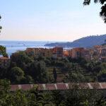 Oświetlone przez słońce zabudowania La Spezii z Morzem Liguryjskim w tle.