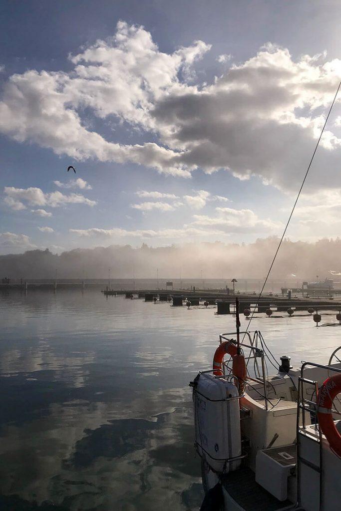 Mgła, chmury i promienie słońca nad opustoszałym Portem Jachtowym w Gdyni.