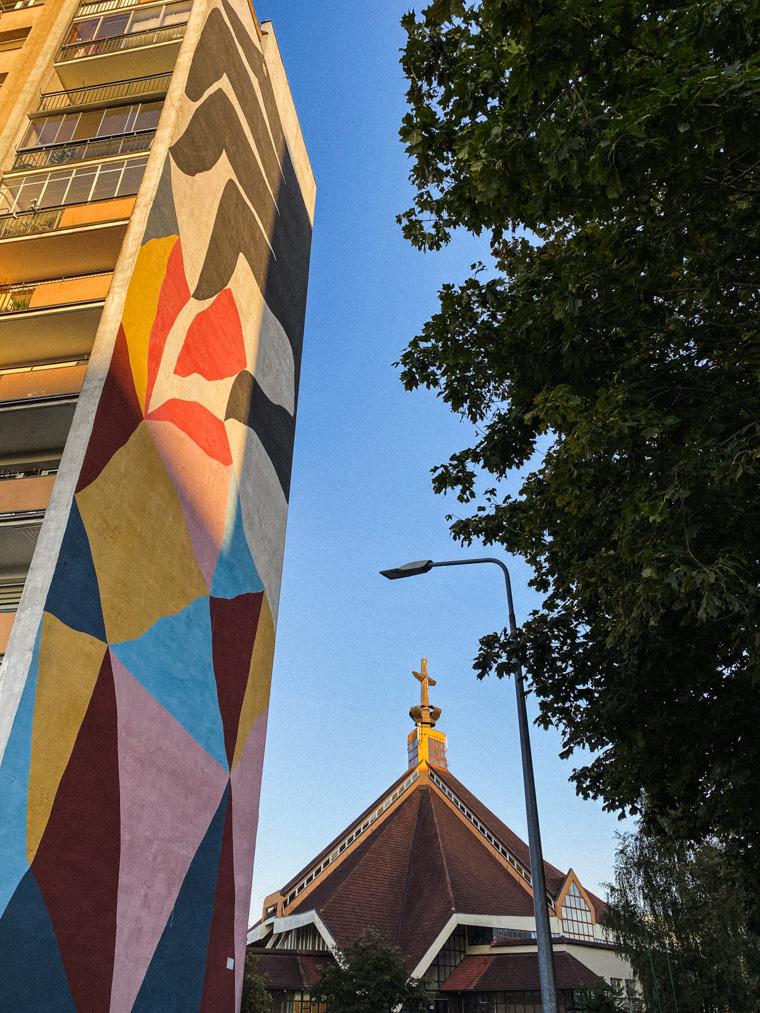 Mural przedstawiający Narcyza, autorem jest Ekta. Z tyłu kościół na Zaspie