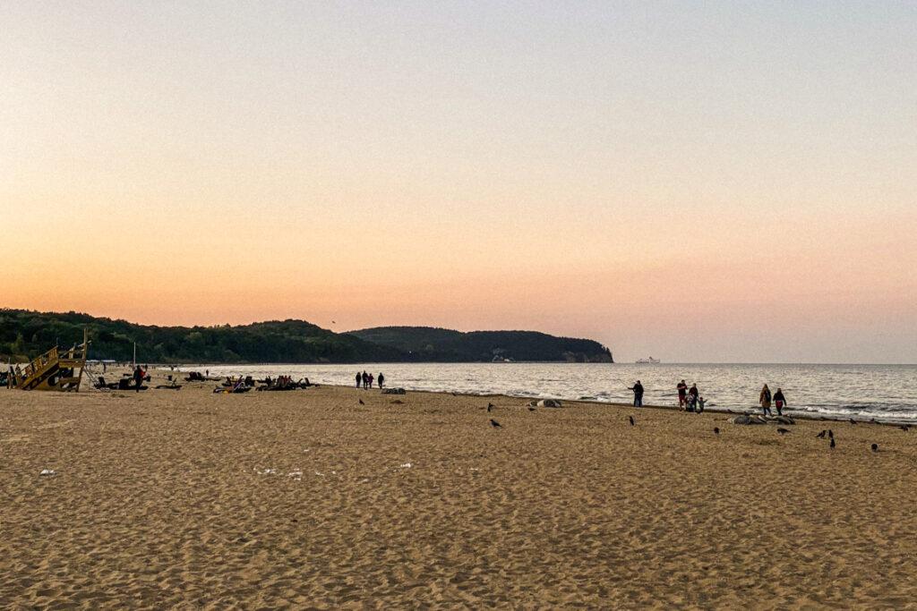 Plaża w Sopocie tuż po zachodzie słońca. W oddali widać klif orłowski i prom Stena Line wpływający do portu w Gdyni