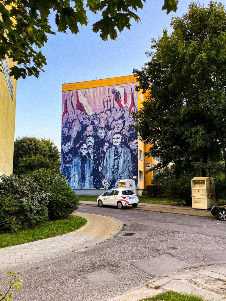 """Mural """"Miłosz w blokowisku"""" przy ulicy Startowej, który powstał na podstawie zdjęcia Janusza Kobylińskiego dokumentującego spotkanie Czesława Miłosza ze stoczniowcami."""